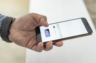 スマートフォンでキャッシュレス決済をする男性の手元の写真素材 [FYI04531437]