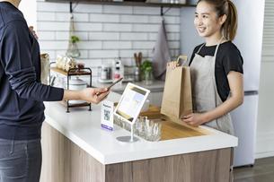 キャッシュレス決済をする客と店員の写真素材 [FYI04531522]