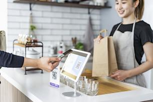 キャッシュレス決済をする客と店員の写真素材 [FYI04531523]
