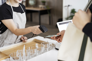 キャッシュレス決済をする客と店員の写真素材 [FYI04531525]