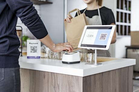 キャッシュレス決済をする客と店員の写真素材 [FYI04531527]