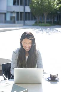 外でパソコンを見て笑っている女性の写真素材 [FYI04532339]
