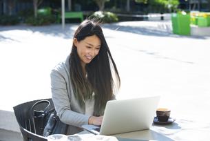 外でパソコンを見ながら笑っている女性の写真素材 [FYI04532340]