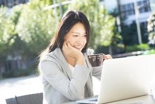 外でコーヒーカップを持ってパソコンの画面を見ている女性の写真素材 [FYI04532345]