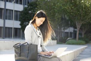 外でパソコンを使って作業をしている女性の写真素材 [FYI04532348]