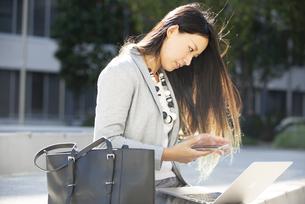 外でパソコンを使って作業をしている女性の写真素材 [FYI04532349]