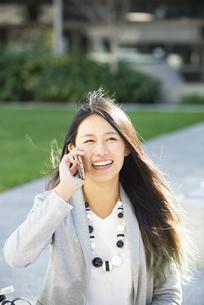 スマホで通話をしている笑顔の女性の写真素材 [FYI04532459]