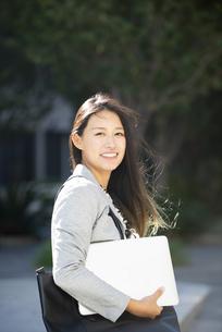 パソコンを抱えて笑っている女性の写真素材 [FYI04532463]