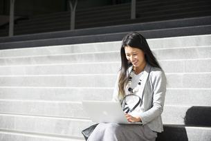 階段に座ってパソコンで作業をしている女性の写真素材 [FYI04532466]