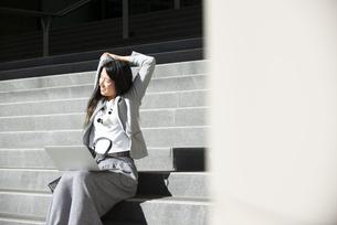 階段に座ってストレッチをしている女性の写真素材 [FYI04532476]