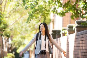 街を手を広げて歩いている女性の写真素材 [FYI04532509]