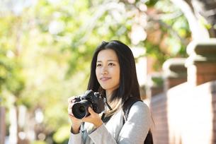 一眼レフのカメラを構えている女性の写真素材 [FYI04532510]