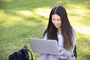芝生の上に座ってパソコンを触っている女性の写真素材 [FYI04532832]