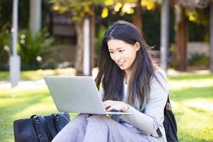 芝生の上に座ってパソコンを触っている女性の写真素材 [FYI04532833]