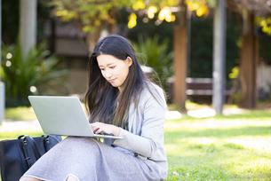 芝生の上に座ってパソコンを触っている女性の写真素材 [FYI04532834]