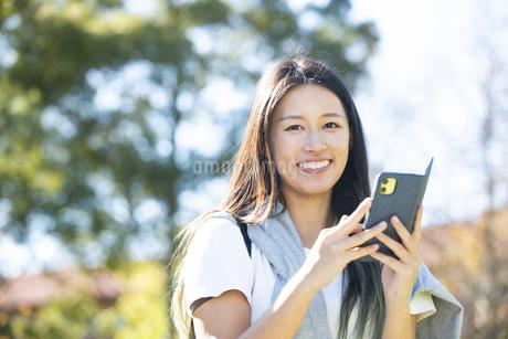 外でスマホを持って笑っている女性の写真素材 [FYI04532876]
