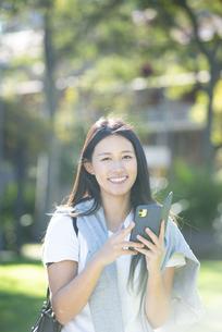 外でスマホを持って笑っている女性の写真素材 [FYI04532879]