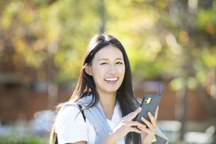 外でスマホを持って笑っている女性の写真素材 [FYI04532880]
