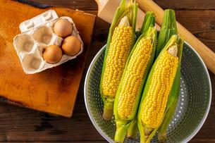 Corn cobs in colander on wooden background.の写真素材 [FYI04533256]
