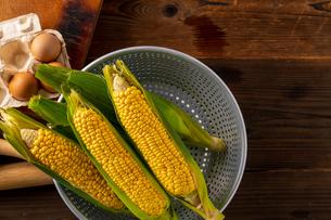 Corn cobs in colander on wooden background.の写真素材 [FYI04533258]