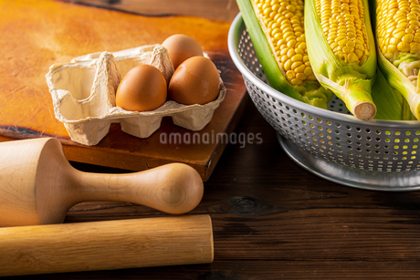 Corn cobs in colander on wooden background.の写真素材 [FYI04533264]