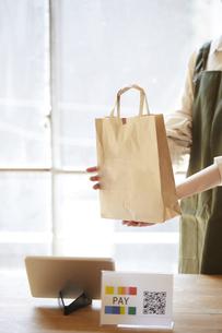 キャッシュレス決済ができるレジの女性店員の写真素材 [FYI04533409]