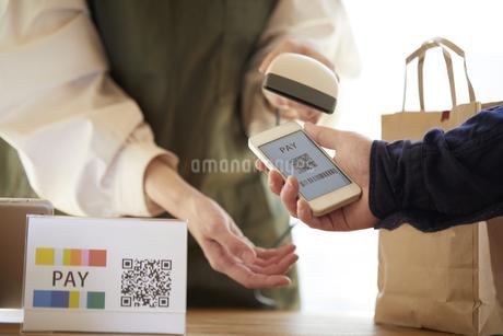 スマートフォンを使って決済をするレジでの手の写真素材 [FYI04533411]