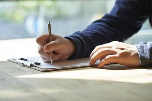 書類にサインをする男性の手元の写真素材 [FYI04533424]