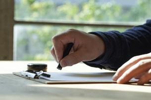 書類に捺印する男性の手元の写真素材 [FYI04533427]