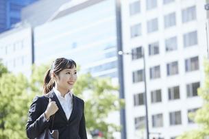 オフィス街を歩く若いビジネスウーマンの写真素材 [FYI04533649]