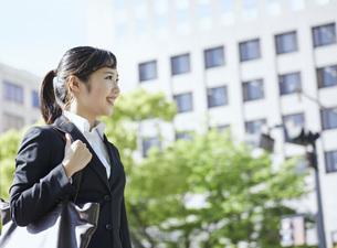 オフィス街を歩く若いビジネスウーマンの写真素材 [FYI04533650]