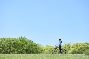 休日にサイクリングを楽しむ若い女性の写真素材 [FYI04533681]