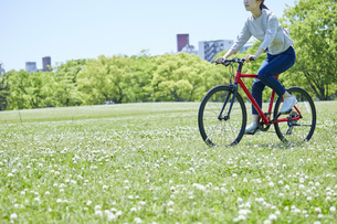 休日にサイクリングを楽しむ若い女性の写真素材 [FYI04533690]