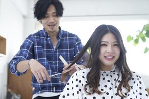 美容室で髪の毛を切る爽やかな美容師の写真素材 [FYI04533729]