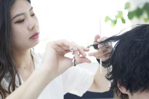 美容室で髪の毛を切る爽やかな美容師の写真素材 [FYI04533736]