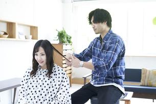 美容室で髪の毛を切る爽やかな美容師の写真素材 [FYI04533745]