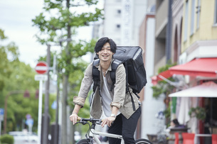 自転車で配達をする若い日本人男性の写真素材 [FYI04533779]