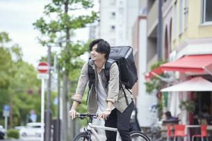 自転車で配達をする若い日本人男性の写真素材 [FYI04533780]