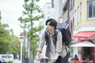 自転車で配達をする若い日本人男性の写真素材 [FYI04533781]