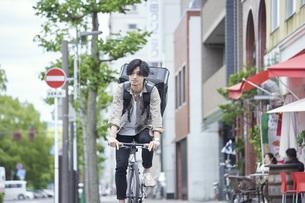 自転車で配達をする若い日本人男性の写真素材 [FYI04533782]