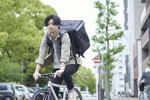 自転車で配達をする若い日本人男性の写真素材 [FYI04533783]
