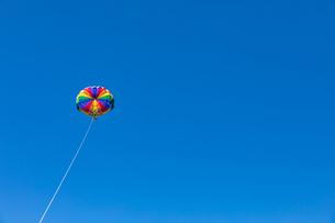 雲ひとつない青空とカラフルなパラセーリングの写真素材 [FYI04536011]