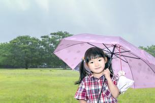 雨降る公園で傘を差しカメラ目線で微笑む幼い少女の写真素材 [FYI04536797]