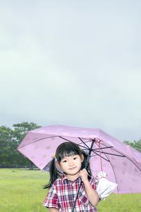 雨降る公園で傘を差しカメラ目線で微笑む幼い少女の写真素材 [FYI04536799]