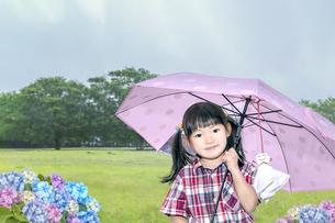 雨降る公園で傘を差しカメラ目線で微笑む幼い少女の写真素材 [FYI04536800]