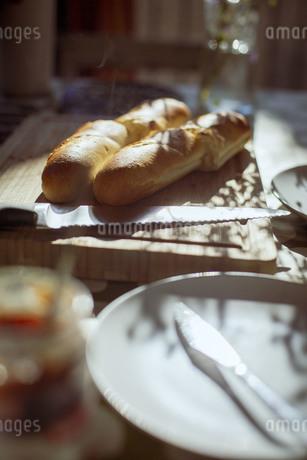 朝の光を受けて食卓に並んだ焼きたてのパンの写真素材 [FYI04538238]