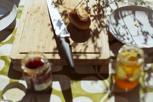 朝の光を受けて食卓に並んだ焼きたてのパンの写真素材 [FYI04538240]