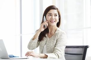 スマートフォンを持つ働く女性の写真素材 [FYI04538340]