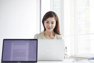 働く女性とノートパソコンの写真素材 [FYI04538367]