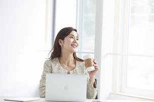 働く女性とノートパソコンの写真素材 [FYI04538381]